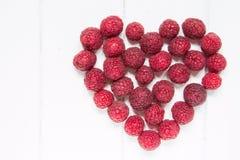 在白色木背景的莓果心脏 免版税库存图片