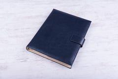 在白色木背景的蓝色皮革笔记本 免版税库存照片