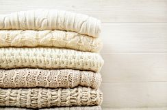 在白色木背景的被折叠的淡色编织毛线衣 免版税库存图片