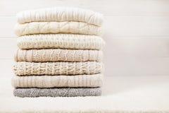 在白色木背景的被折叠的淡色编织毛线衣 库存图片
