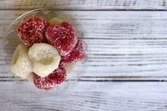 在白色木背景,甜点的白色和红色心形的橘子果酱为情人节 免版税库存图片