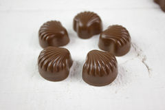 在白色木头的巧克力糖 免版税图库摄影