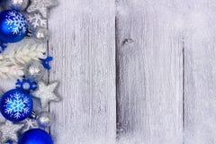 在白色木头的蓝色和银色圣诞节装饰品边边界 免版税图库摄影