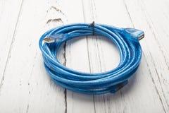 在白色木头的蓝色usb缆绳 免版税库存照片