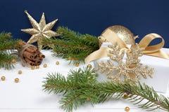 在白色木头的金黄圣诞节装饰 库存照片