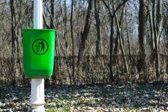 在白色杆的绿色垃圾箱在公园-春天定期的午间 免版税库存图片