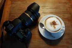 在白色杯子和照相机的热的热奶咖啡 免版税库存图片