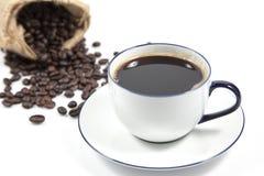 在白色杯子和迷离咖啡种子的咖啡在背景的大袋 免版税库存图片