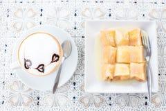 在白色杯子和面包的热的咖啡上等咖啡拿铁在木背景 库存图片