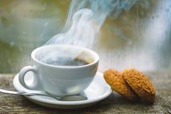 在白色杯子或杯子的新鲜的煮的咖啡在窗台 湿玻璃窗和杯子热的咖啡因饮料 咖啡饮料 免版税库存图片