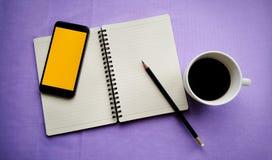 在白色杯子的咖啡有学报书和巧妙的电话的 库存照片