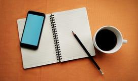 在白色杯子的咖啡有学报书和巧妙的电话的 图库摄影