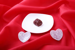 在白色杯子的咖啡用在红色背景的巧克力果仁糖 免版税库存照片