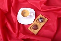 在白色杯子的咖啡用在红色背景的巧克力果仁糖 库存图片