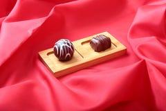在白色杯子的咖啡用在红色背景的巧克力果仁糖 库存照片