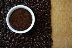 在白色杯子的咖啡豆在粗麻布 库存照片