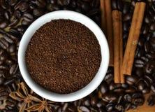 在白色杯子的咖啡豆用香料 图库摄影