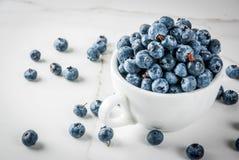 在白色杯子的新鲜的未加工的有机农厂蓝莓在白色大理石ki 库存图片