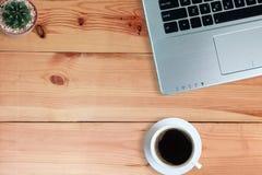 在白色杯子的无奶咖啡和便携式计算机和仙人掌在木地板,顶视图上 免版税库存图片