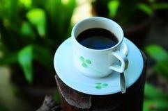 在白色杯子的无奶咖啡有自然庭院的 免版税库存图片
