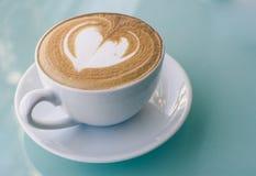 在白色杯子的热奶咖啡在绿色玻璃桌,被创造的牛奶泡沫上 库存照片