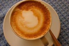 在白色杯子的热奶咖啡在蓝色桌上 图库摄影