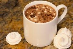 在白色杯子的热巧克力用在棕色大理石的自创法国蛋白甜饼蛋白软糖 免版税库存图片