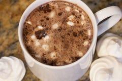 在白色杯子的热巧克力用在棕色大理石的自创法国蛋白甜饼蛋白软糖 免版税库存照片
