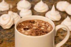 在白色杯子的热巧克力用自创法国蛋白甜饼蛋白软糖在背景中在棕色大理石 图库摄影