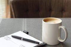 在白色杯子的热的咖啡latte有学报的书的 免版税图库摄影