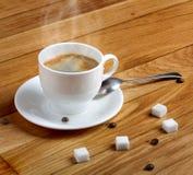 在白色杯子的热的新鲜的咖啡用在木桌上的糖 免版税库存照片