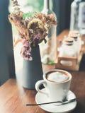 在白色杯子的热的热奶咖啡咖啡在与花的木桌上 图库摄影