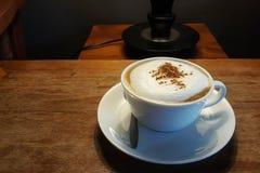 在白色杯子的热的热奶咖啡在桌上 库存图片
