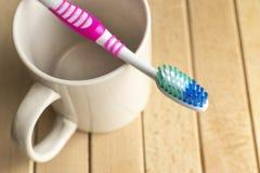 在白色杯子的牙刷 库存照片