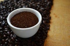 在白色杯子的碾碎的咖啡用咖啡豆在背景中 库存照片
