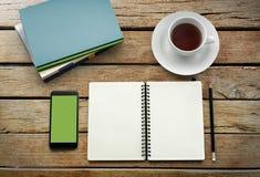 在白色杯子的茶有学报书和智能手机的 免版税图库摄影
