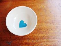 在白色杯子的蓝色心脏 免版税库存照片