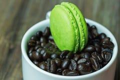 在白色杯子的蛋白杏仁饼干用咖啡豆 免版税库存图片