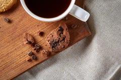 在白色杯子,在切板特写镜头,选择聚焦的巧克力曲奇饼的早晨咖啡 免版税库存照片