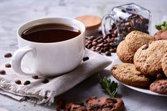 在白色杯子,在手织的餐巾,特写镜头,选择聚焦的巧克力曲奇饼的早晨咖啡 免版税库存图片