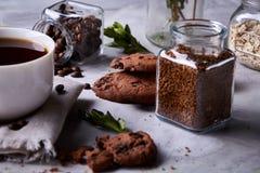在白色杯子,在手织的餐巾,特写镜头,选择聚焦的巧克力曲奇饼的早晨咖啡 图库摄影