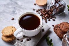 在白色杯子,在手织的餐巾,特写镜头,选择聚焦的巧克力曲奇饼的早晨咖啡 免版税库存照片