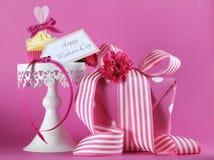 在白色杯形蛋糕立场的愉快的母亲节桃红色心脏杯形蛋糕与礼物 库存图片