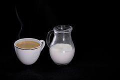 在白色杯牛奶的咖啡在黑背景的一个小水罐 免版税库存照片