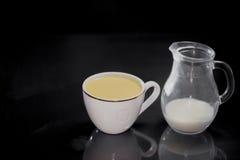 在白色杯牛奶的咖啡在黑背景的一个小水罐 库存照片