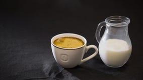 在白色杯牛奶的咖啡在黑背景的一个小水罐 图库摄影