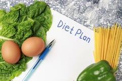 在白色板料和健康食品的题字用餐计划 在视图之上 免版税库存图片