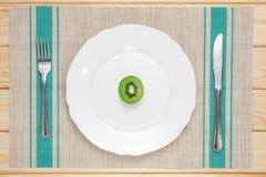 在白色板材、匙子和叉子的新鲜的猕猴桃 免版税库存照片