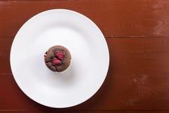 在白色板材上的平的位置用巧克力杯子蛋糕松饼用莓 免版税库存照片
