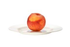 在白色板材关闭的美丽的桃子 免版税库存照片